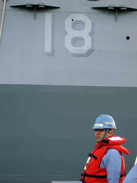 This photo shows the number 18 written on the side of a large ship.