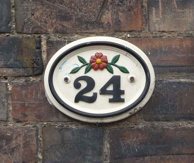 This photo shows the number 24 and a flower used as a ceramic house number.