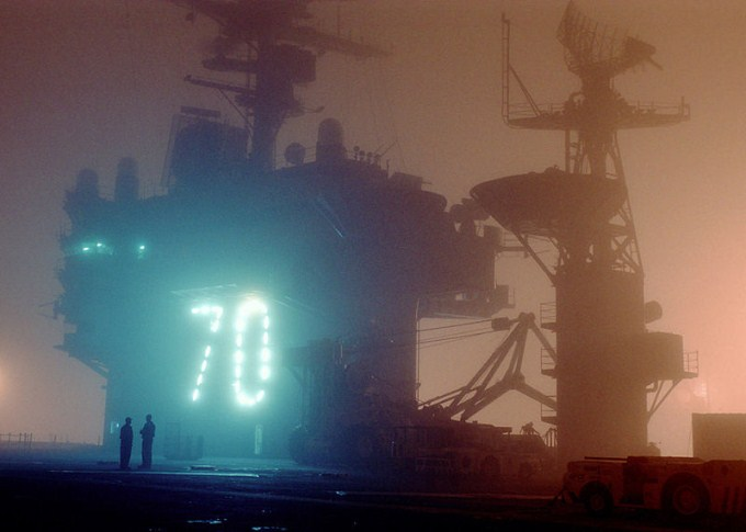 This photo shows the number 70 illuminated through the fog on the deck of an aircraft carrier behind two men.