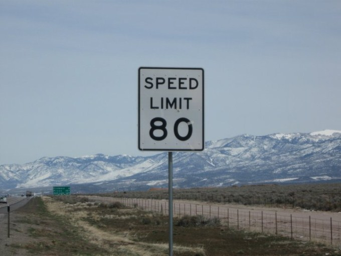 This photo shows the number 80 on a speed limit sign next to the open ...