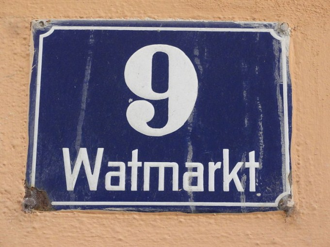 This photo shows the number 9 written in white on a blue house number plaque.